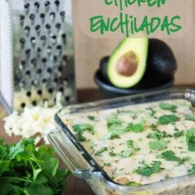 Casserole dish of Spicy Avocado Chicken Enchiladas with a cheese grater and avocados in the background