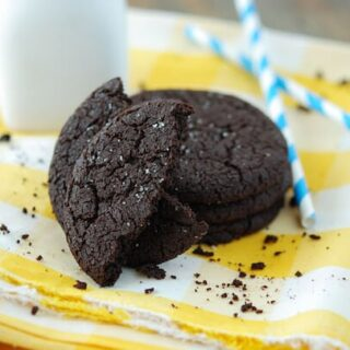 Image of dark chocolate cookies on a yellow napkin with blue straws and a glass of milk