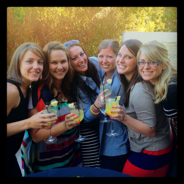 A group of women holding drinks and smiling