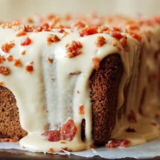 close-up shot of an espresso poundcake with maple bacon icing dripping down the sides
