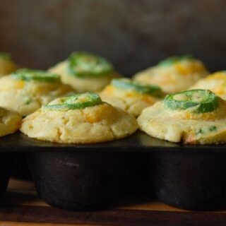 Jalapeno Sweet Corn Muffins - each topped with a slice of jalapenos in a muffin tin
