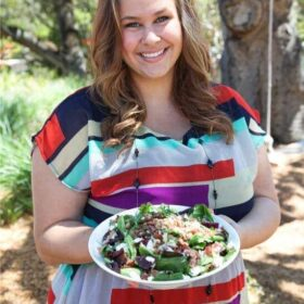 A woman in a colorful dress holding a white plate filled with salad