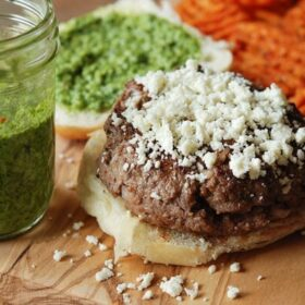 Cilantro Chimichurri Burger topped with Cotija cheese served with Sweet Potato Fries. Mason jar of Cilantro Chimichurri next to burger.