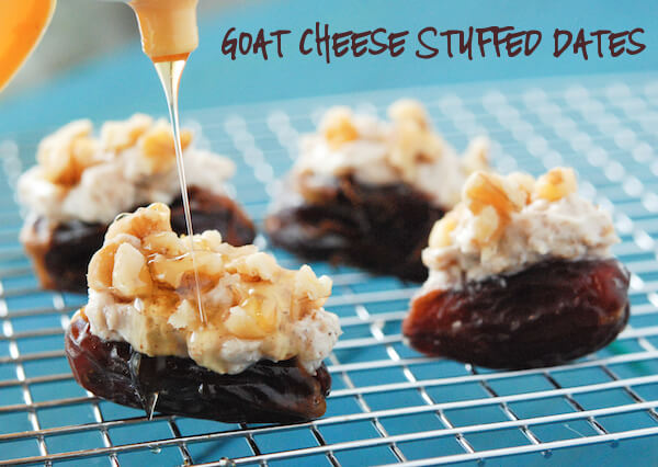 Four Goat Cheese Stuffed Dates Sitting on a Metal Rack Over a Teal Surface