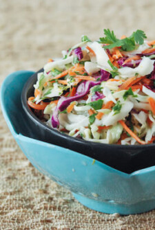 Cilantro Citrus Slaw set in a black bowl set in a blue tuliped dish