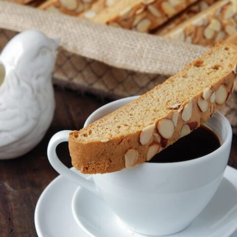 Almond Biscotti over a white coffee cup and white dishes - basket of Almond Biscotti in background