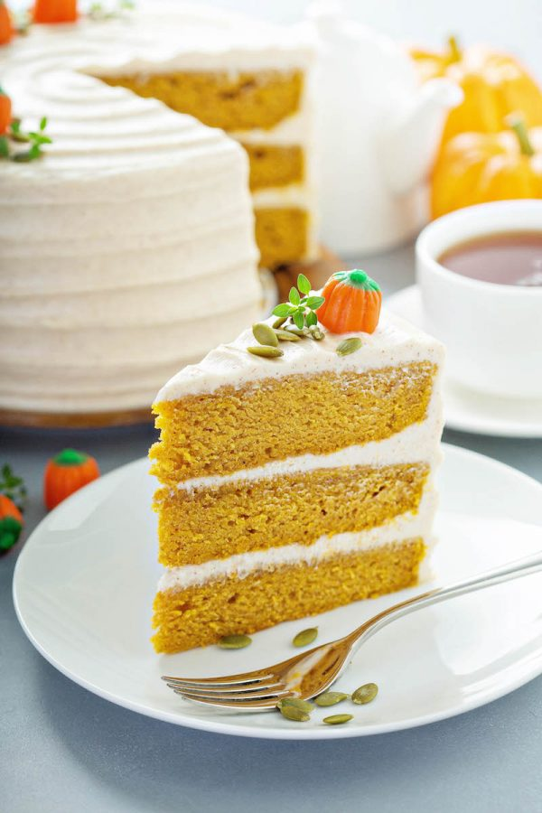 Pumpkin Cake slice with three layers and cream cheese icing on a plate.