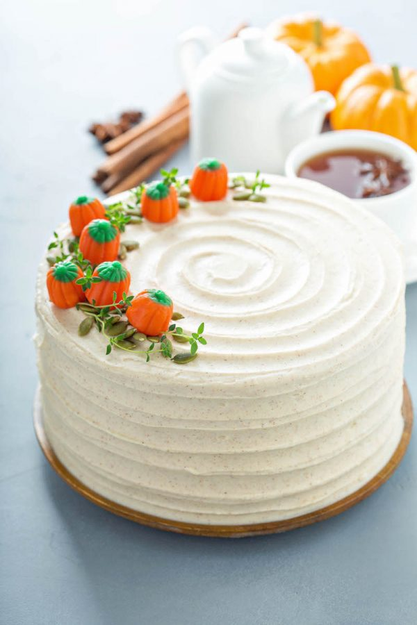 Pumpkin Cake with cream cheese icing with pumpkin candies on top with thyme like a vine.