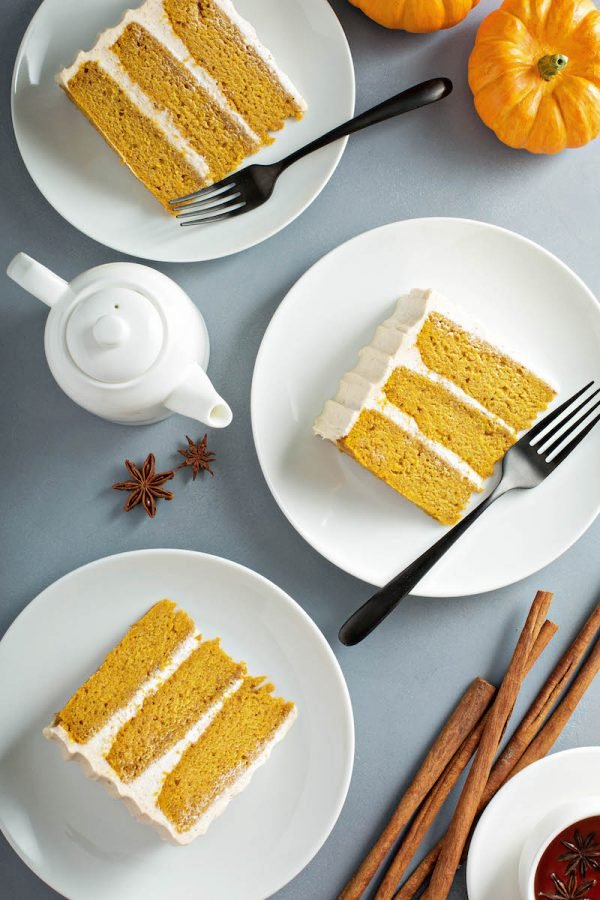 Three slices of pumpkin cake on white plates.