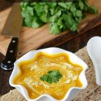 Butternut Squash Coconut Curry Soup in a white bowl topped with coconut cream