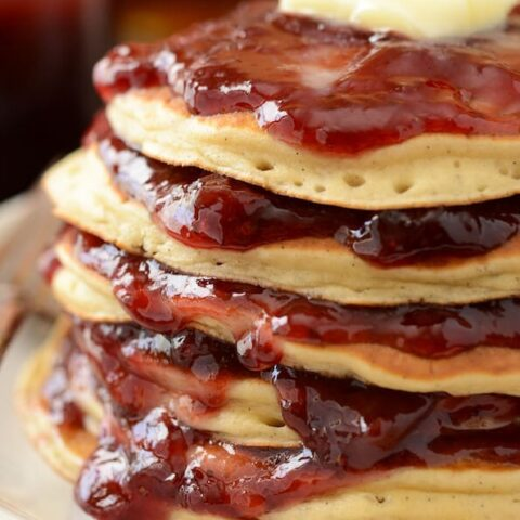 Sour Cream Jam Stacked Pancakes topped with jam and butter on a white plate