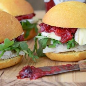 Close up of Turkey Sliders loaded with brie, arugula and a savory homemade cranberry chutney