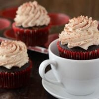 A Spicy Hot Cocoa Cupcake in a White Mug Beside Two More Frosted Cupcakes