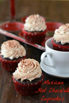 Mexican Hot Chocolate Cupcakes topped with shaved chocolate in a white coffee cup