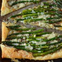 Slices of Red Onion, Asparagus & Blue Cheese Tart topped with cheese