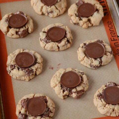 Peanut Butter Cookies topped with Reese's Cups sit on a baking sheet