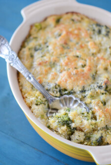 Cheesy Broccoli Quinoa Casserole in a yellow casserole dish with a silver serving spoon