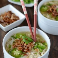 Chicken Pho in a white bowl with red chopsticks