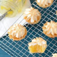 Six mini lemon meringue pies on a metal rack. One pie is cut in half showing inside lemon filling.
