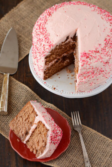 Slice of strawberry frosted cake on a red plate