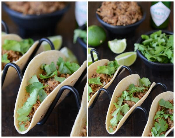 Pork Carnitas in a black taco holder with ingredients behind them
