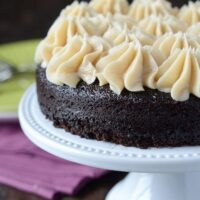 A Dark Chocolate Guinness Cake with Dollops of Bailey's Frosting on a White Cake Platter