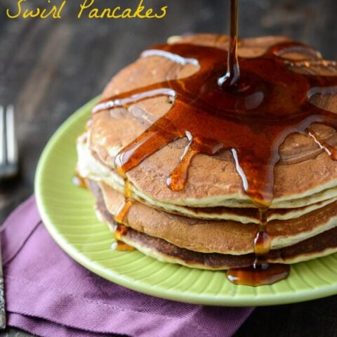 A stack of banana pancakes on a green plate with syrup being poured on top