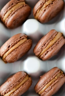 Chocolate Biscoff Macarons in a white ceramic egg container.
