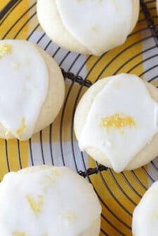 Meltaway Lemon Cookies on a black cooling rack set on a yellow and white tablecloth