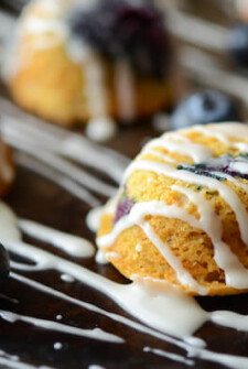 Blueberry Corn Muffins with a drizzled Vanilla Glaze on a dark surface