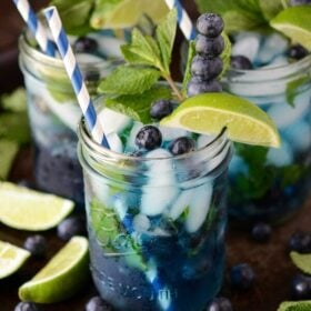 Blueberry Mojitos with limes and blueberries on a dark surface