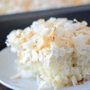 A close up shot of a big slice of Coconut Sheet Cake