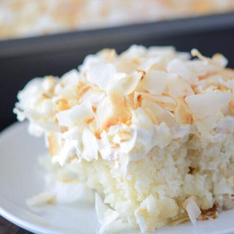 A close up shot of a big slice of Coconut Sheet Cake