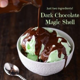 DIY Dark Chocolate Magic Shell being poured over Mint Chocolate Chip Ice Cream in a white bowl with a spoon.