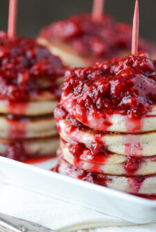 Stacks of Homemade Pancakes with Raspberry Sauce on a white platter.