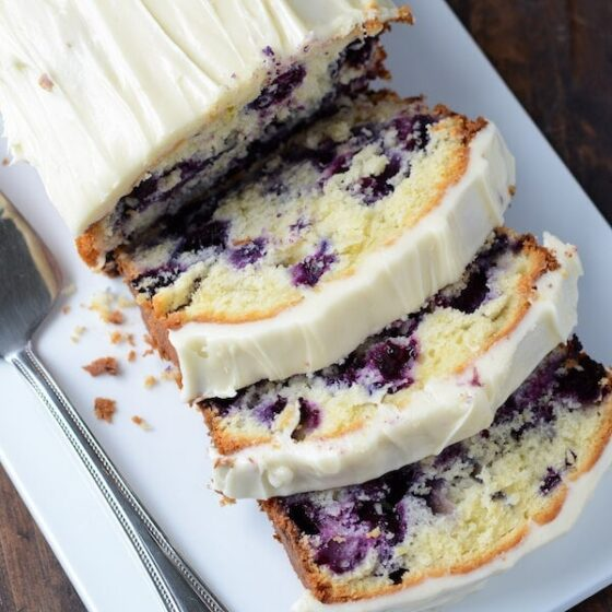Blueberry Lime Cream Cheese Pound Cake sliced on a white platter.