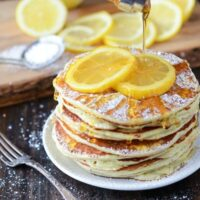 Maple syrup is poured over a plate of piled up pancakes with sliced lemons.