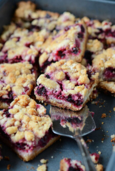 Blackberry Pie Bars topped with crumbles on a sheet pan with a serving utensil.