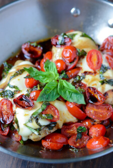 Caprese Chicken topped with balsamic, basil, and cheese in a pan.