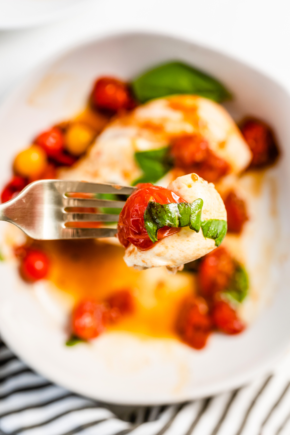 Forkful of chicken with a cherry tomato.