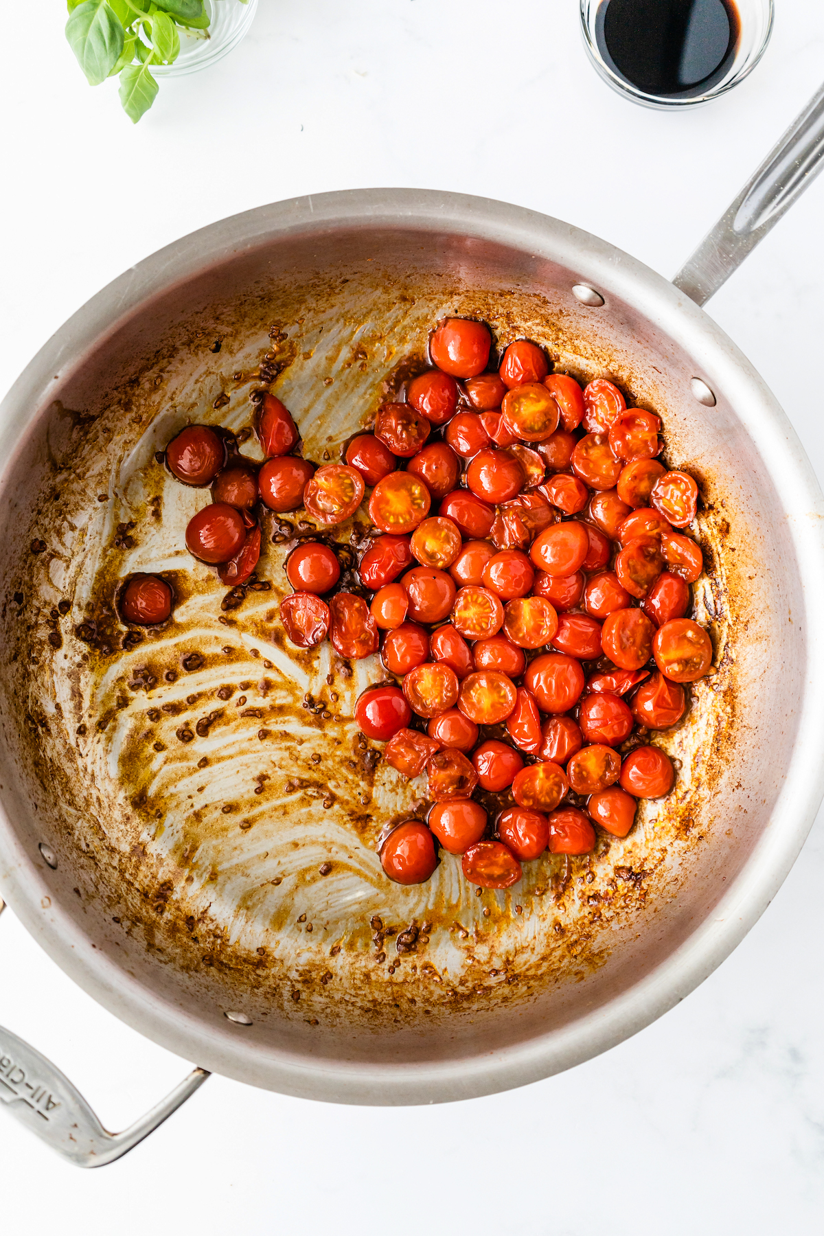 Cherry tomatoes sautéed in a pan.
