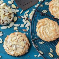 Ultimate Almond Cookies on a black rack with scattered almonds.