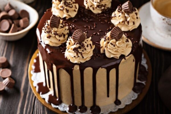 Chocolate and Peanut Butter Dream Cake -- it tastes like a giant Reese's cup in cake form! Start with a crazy moist, rich chocolate three layer cake with creamy peanut butter frosting and top it with a sweet dark chocolate glaze! #Chocolate #Cake #PeanutButter