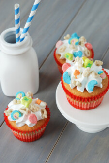 Three cupcakes in red wrappers topped with marshmallow frosting and lucky charms