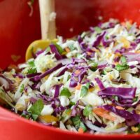 Spicy Mango Slaw in a red bowl with a wooden spoon.