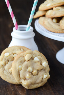 Two White Chocolate Macadamia Nut Cookies set up against a small white ceramic milk jug.