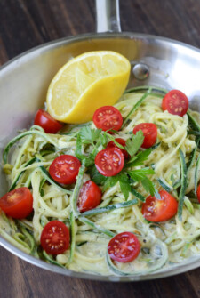 Zucchini Pasta in a Lemon Cream Sauce with half a lemon in a pan.