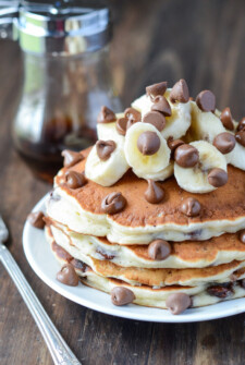 Stack of Banana Chocolate Chip Pancakes on a white plate topped with bananas and chocolate chips.