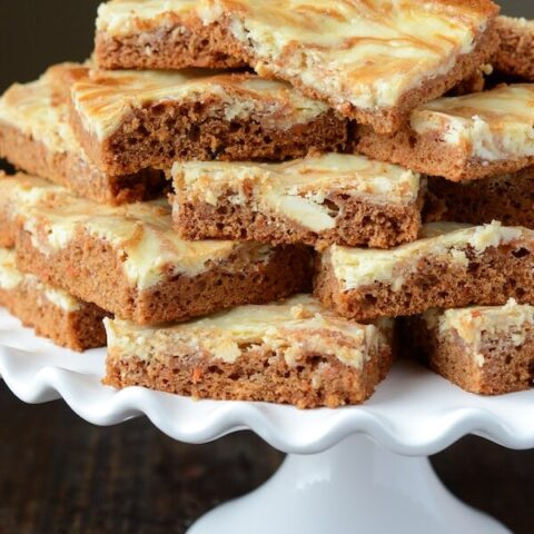 Carrot Cake Cheesecake Swirl Bars on a white cake stand