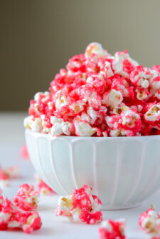 Hot Tamale Popcorn in a white bowl and scattered popcorn on a white surface
